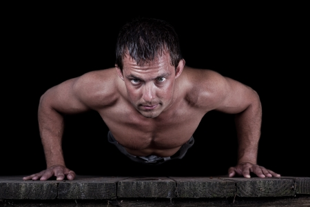 Dramatic portrait isolated on a black background of a young  male doing push-ups photo