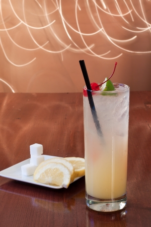tom collins: traditional cocktail on a bartop with sugar cubes and lemon slices on the side, tom collins or vodka collins