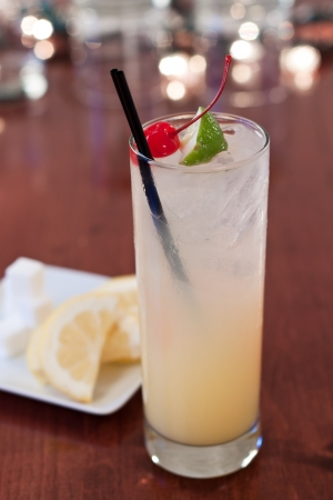 tom collins: traditional tom collins served on a bar top in a tall glass with cherry and lime wedge garnish Stock Photo