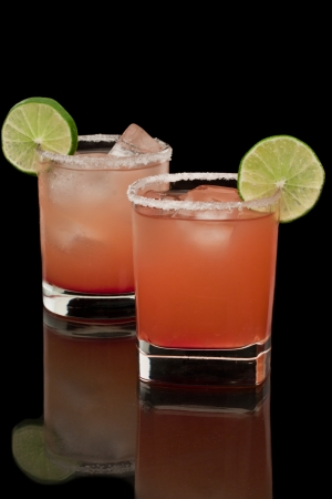 margaritas: Pink and red drinks on a reflective surface with a salt rim and a lime garnish
