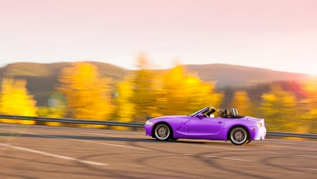 Beautiful woman driving a convertible sports car with changing colors in autumn