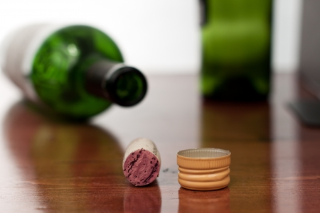wine cork and screw cap on a bar top with blured bottles in the background Stock Photo