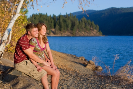 young couple sitting on a rock smiling and enjoying the view Stock Photo - 15738790