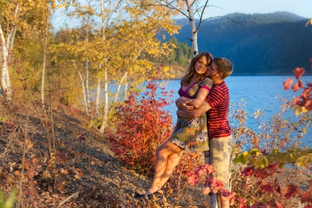adorable portrait of a young couple by the lake with changing foliage photo