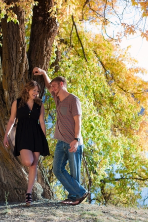 young couple flirting underneath a large tree mid autumn in idaho photo