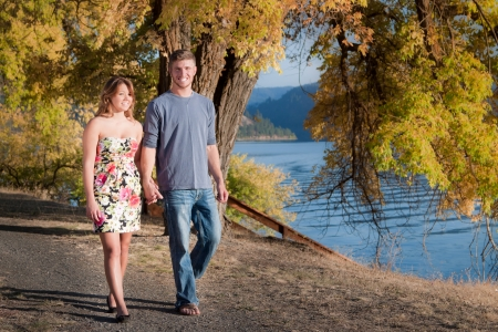 young couple walking mid autumn in idaho next to the lake photo