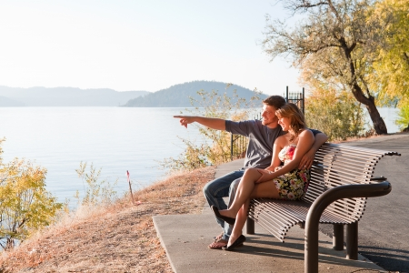 young cute couple sitting on a bench enjoying the sunset in idaho Stock Photo