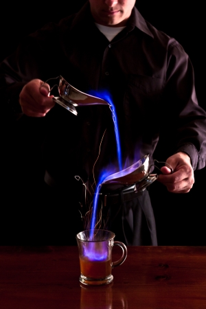 the flair: bartender making a flaming coffee drink with bright blue flames in a dark bar