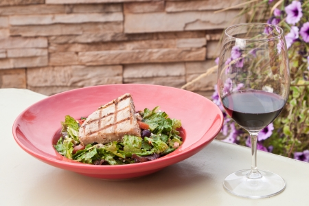 tuna salad served outside with flowers in the back and red wine on the side photo
