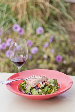 seared ahi tuna salad served outdoors with a glass of wine photo