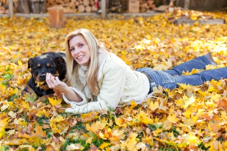 woman and her dog outdoors laying on golden autumn leaves photo