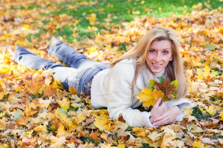 Beautiful woman laying on golden maple leaves  early autumn photo