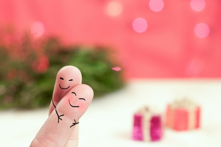 hugging fingers with a holiday background with red, green and presents Stock Photo