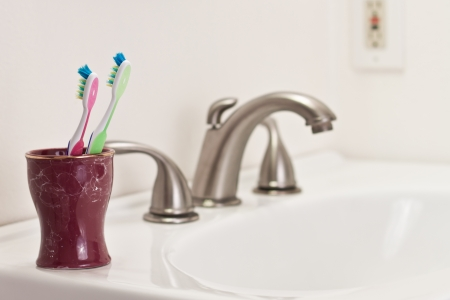 concept with two toothbrushes in a bathroom, one green and one pink, commitment step photo