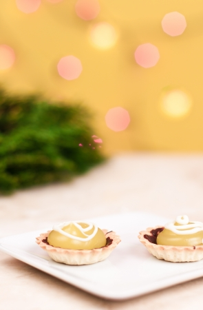 two bite size lemon tarts on a white plate with green branches on th ebackground Stock Photo - 16484133