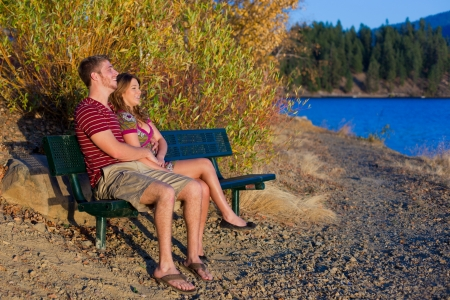 couple on a bench lake side with sunset view photo