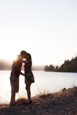 young couple kissing on the shore with the sun behind them, dramatic and low color Stock Photo