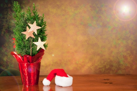 magical christmas scene background with a santa hat and a small tree with stars Stock Photo - 16710436