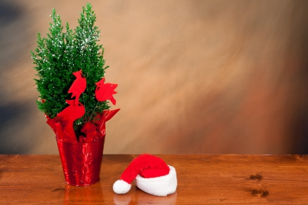 plain christmas background with a small tree and  santa's hat Stock Photo - 16710430