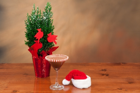 Christmas drink on a bar top with a santa hat  behind it and a small tree to the side Stock Photo - 16710434
