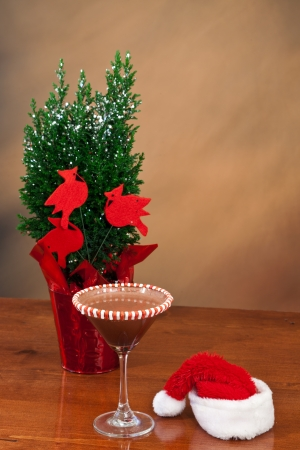 ocd: Christmas drink on a bar top with a santa hat  behind it and a small tree to the side