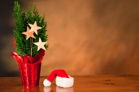 plain christmas background with a small tree and  santa's hat Stock Photo - 16747403