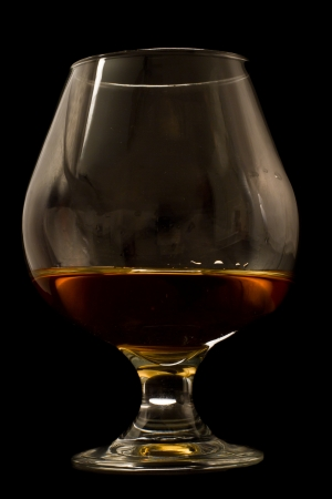 brandy served in a snifter isolated on a black background Stock Photo - 16847479
