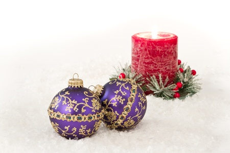 Purple christmas ornaments in snow with a red holiday candle behind them Stock Photo - 16847488