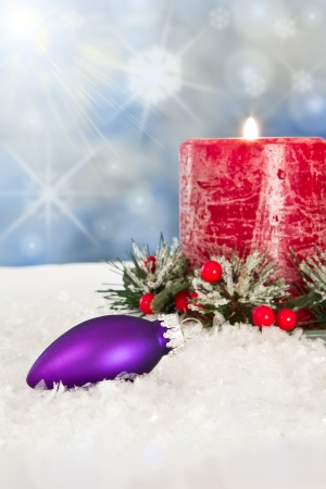 christmas scene with a purple ornament and a red candle on white snow and a little magic Stock Photo - 16847498