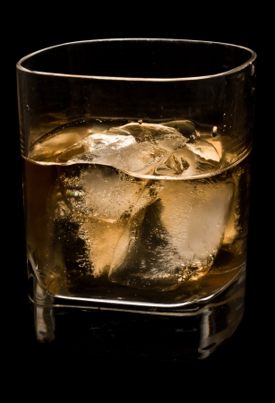 whiskey in a glass with ice backlit and isolated on a black background