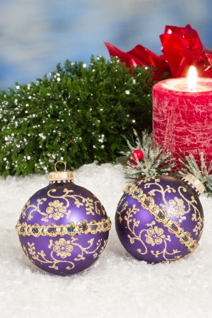 Purple christmas ornaments in snow with a red holiday candle behind them Stock Photo - 16847492