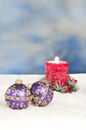 Purple christmas ornaments in snow with a red holiday candle behind them Stock Photo - 16847503