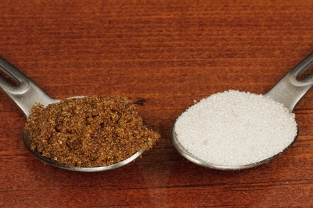 fructose: comparison between brown and white sugar on a teaspoon over a wooden table Stock Photo