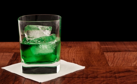 glass of green whiskey served on the rocks, bar top isolated on a black background Stock Photo - 16981866