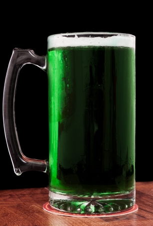 Green Saint Patricks beer isolated on a black background served in a chilled mug photo
