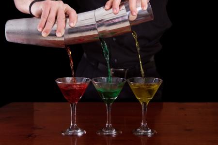 bar tierno verter tres martinis de colores diferentes en un movimiento fluido