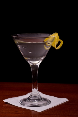 glass topped: martini garnished with a lemon twist isolated on a black background