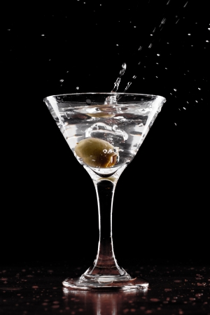 glass topped: vodka martini isolated on a black background with an olive splashing and air bubbles Stock Photo