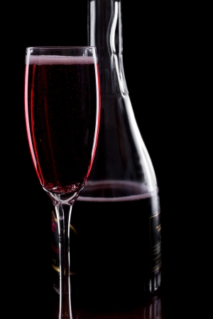 rose champagne served in  flutes isolated on a black background, dark setting photo