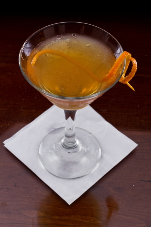 serving a manhattan cocktail garnished with an orange twist on a dark bar setting photo