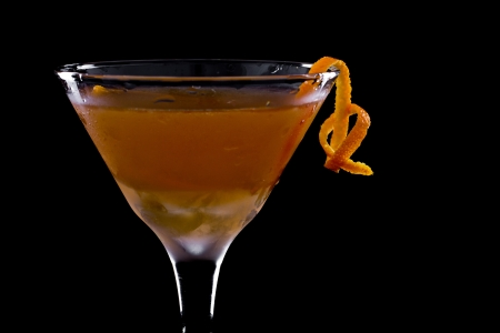 serving a manhattan cocktail garnished with an orange twist on a dark bar setting Stock Photo - 17171022