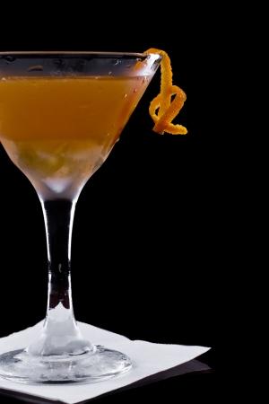 serving a manhattan cocktail garnished with an orange twist on a dark bar setting Stock Photo - 17171017