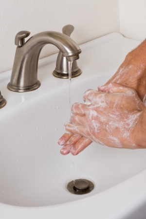 closeup of two adult hands washing with soap and running water at home