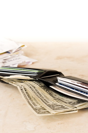 spending full: a close up view of a wallet with money and credit cards