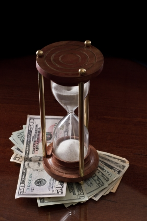 concept of an hour glass with time passing over money