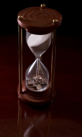 fiscal cliff: hour glass on a dark background with american money in it Stock Photo