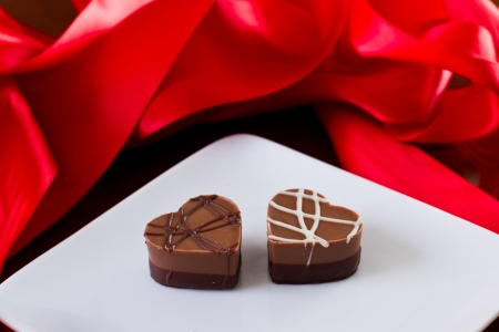 shaped: heart shaped chocolates on a white plate with red silk on the back