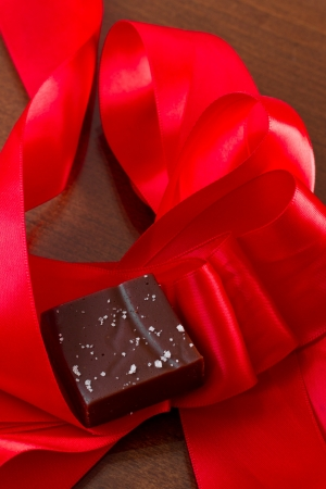 home made caramel with sea salt with a red silk bow Stock Photo - 17445877