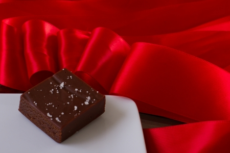 home made caramel with sea salt with a red silk bow Stock Photo - 17445896