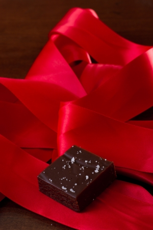 home made caramel with sea salt with a red silk bow Stock Photo - 17445917